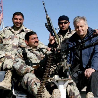 Rauli Virtanen istuu kolmen henkivartijan kanssa auton lavalla Irakissa.