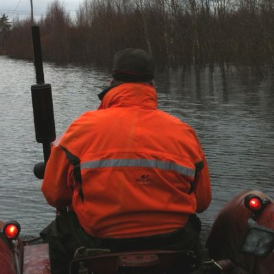 Mies ajaa Kiiminkijoen tulva-alueella traktoria.