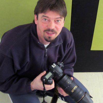 Kuvassa mies järjestelmäkameran kanssa