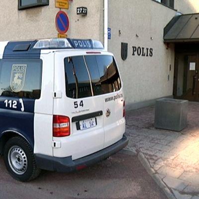 Ahvenanmaan poliisi seisoo autonsa vieressä.