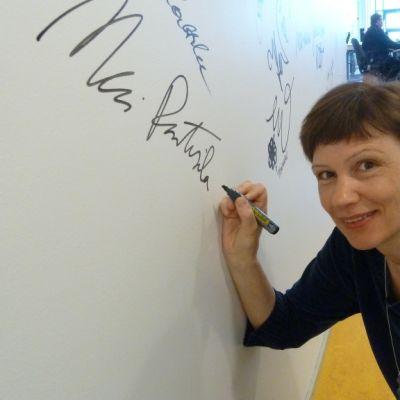 Mari Rantasila kirjoittaa nimikirjoitustaan seinään