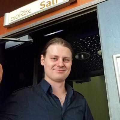 Elokuvatuottaja ja -levittäjä Miika J. Norvanto avaa elokuvasalin ovea ja hymyilee.