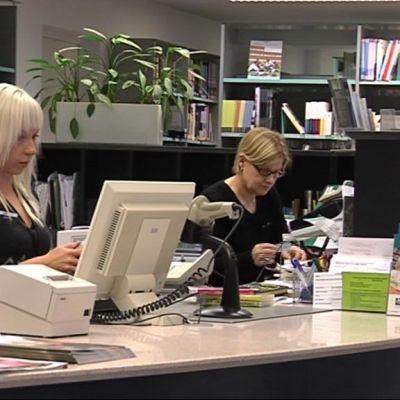 Henkilökuntaa Joensuun kirjaston lainaustiskillä.