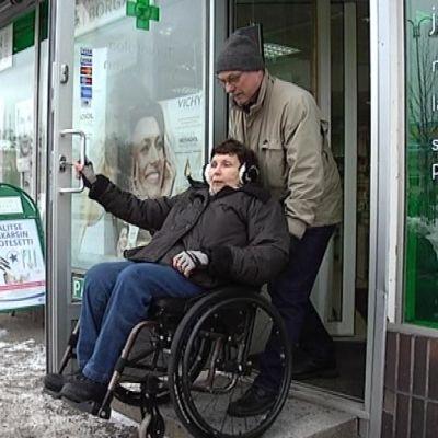 Keskustan Apteekkiin ei ole pyörätuolilla asiaa ilman avustajaa. Marja-Terttu Lindforsia auttaa Otto Räsänen.