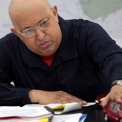 Hugo Chavez ohjailee punaista auton pienoismallia.