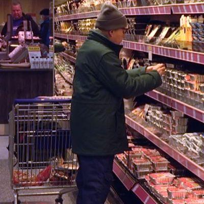 Asiakas ottaa marketin hyllystä einesruokapakkauksen.