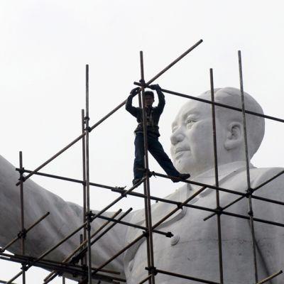 Työntekijät poistavat rakennustelineitä Mao Zedongia esittävän valkoisen marmoripatsaan ympäriltä Chengdussa tammikuussa 2007.