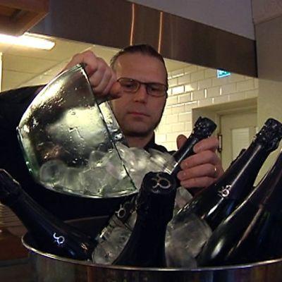 Erik Forsman kaataa jäitä kuohuviiniastiaan Ravintola Puistolassa Oulussa.