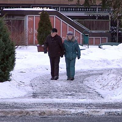 Vanhempi pariskunta kävelee hiekoitettua kävelyväylää puistossa.