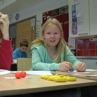 Lapset laskevat matematiikan tehtäviä käyttäen apunaan muovihedelmiä.