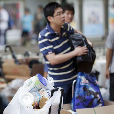 Nainen odottaa mannerkiinaan suuntaavaa junaa asemalaiturilla Hongkongissa 31. tammikuuta 2013 mukanaan kassillinen äidinmaidonkorviketta.