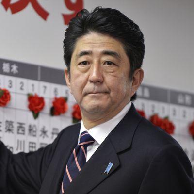 Shinzo Abe asettaa ruusua kiinni nimitauluun.