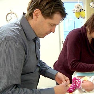 Kuvassa vauva makaa hoitopöydällä, äiti rahoittaa vauvaa tutilla, tutkimushoitaja laittaa jalkaan rokotuskohtaan laastaria
