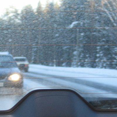Kuvassa auton takalasin läpi kuvattu takaa tuleva auto. Lumi pöllyää.