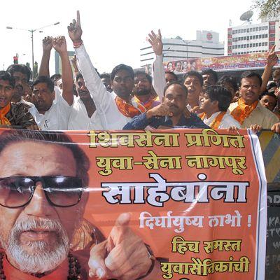 Intialaisia kannustamassa banderollin takana.