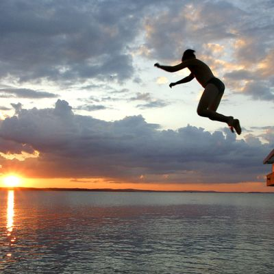Boy jumping off a dock at sunset