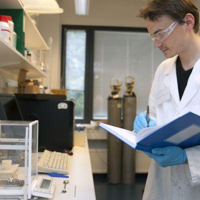 Tutkija mittaa ja punnitsee akkuelektrodimateriaaleja.