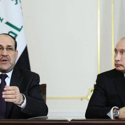 Maliki ja Putin maidensa lippujen edustalla.