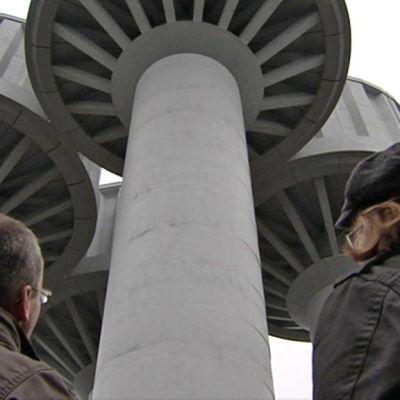 Vesitornit alaviistosta kuvattuna kahden miehen takana.