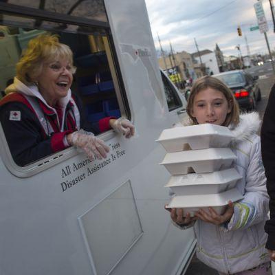 Cathy Wooden kävi hakemassa Michelle-tyttärensä kanssa ilmaisia aterioita Punaisen Ristin kojulta, jossa heitä palveli vapaaehtoinen Kay Ralph.