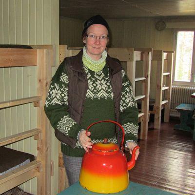 Marika Hänninen seisoo majassa vanhan nokikahvipannun kanssa