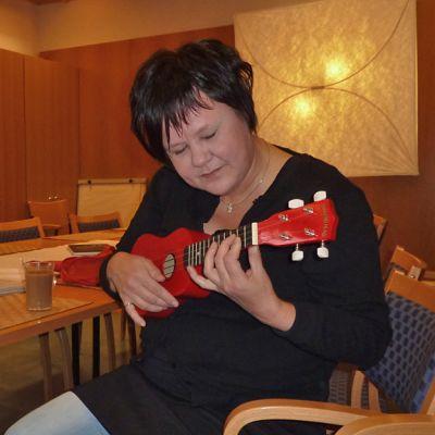 Tarja Kerttula soittaa ukulelea.