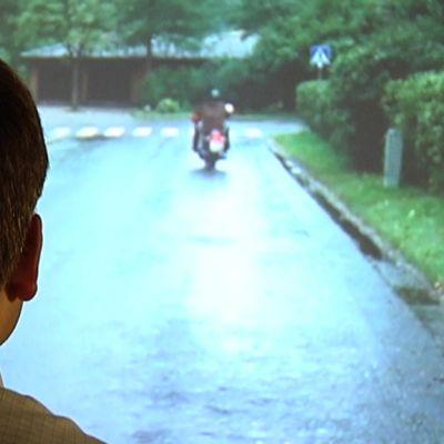 Mies katsoo elokuvaa valkokankaalta.