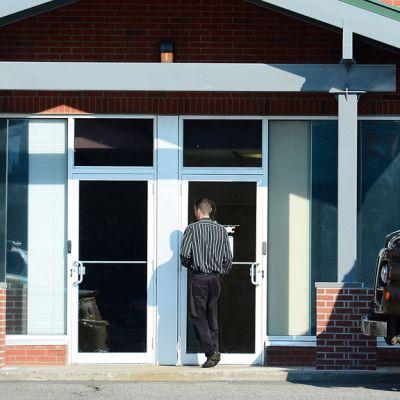 Mies rakennuksen ovella.