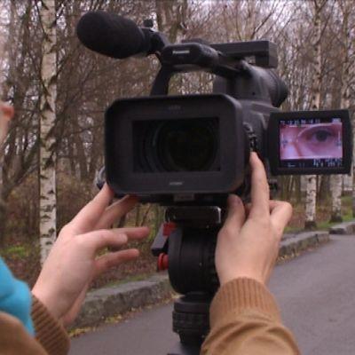 Nainen seisoo videokameran edessä.