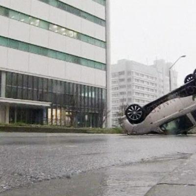 Taifuuni Jelawatin tuhoja Okinawassa. Auto ylösalaisin kadulla.