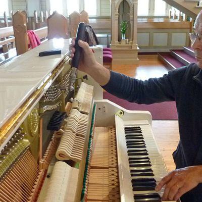 Hannu Aitoaho virittää pianoa Kajaanin kirkossa.
