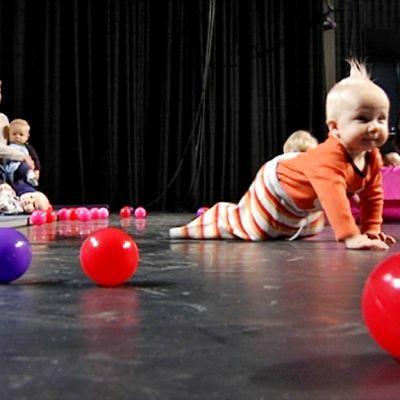 Kirkkaanväriisiä palloja lattialla, poikavauva konttaa niiden takana.