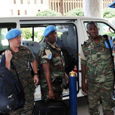 YK:n sotilastarkkailijoita auton vieressä.