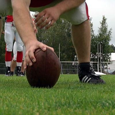 Amerikkalaisen jalkapallon pelaaja pitelee palloa