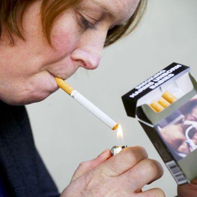 Nainen sytyttää tupakkaa kädessään aski, jossa on letkuihin kytketyn vauvan kuva.