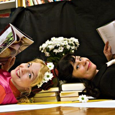 Heli Laaksonen ja Päivi Luosma makaavat lattialla kirjoja lukien.