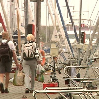 Kaksi ihmistä kävelee Hangon Itäsataman laiturilla, johon on kiinnittynyt paljon veneitä.