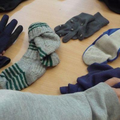 Sukkia, hanskoja ja tossuja pöydällä.