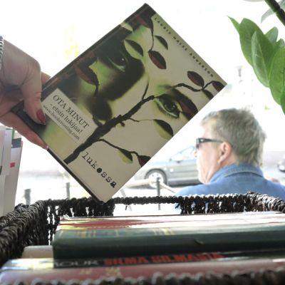 Kuvassa nainen pitää kädessään kirjaa