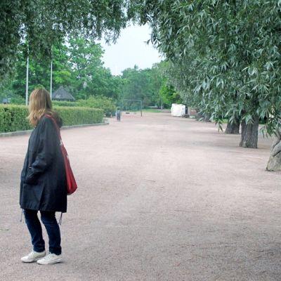 Nainen katsoo olkansa ylitse kävelytiellä.