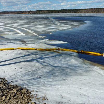 Öljypuomit  osittain jääpeitteisen vahinkoalueen ympärillä vesistössä.