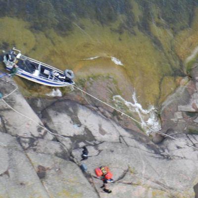 Vedellä täyttynyt vene kallion laidalla ja pelastajia noutamassa matkustajia.