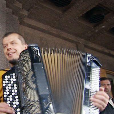 Kimmo Pohjonen soittaa romanien kanssa kadulla Helsingissä.