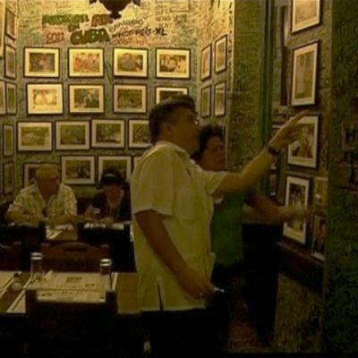 Pariskunta katselee valokuvia baarin seinällä