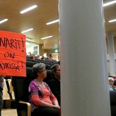 Nainen terveysaseman lakkauttamista vastustavan kyltin kanssa kuntalaisten kuulemistilaisuudessa Jyväskylässä.