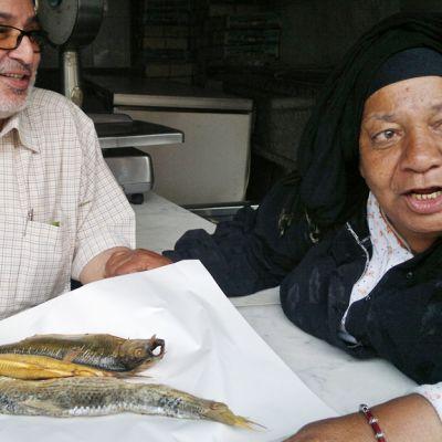 Hagg Abdou ja Madame Nadia pöydän ääressä, jossa on muumiokalaa paperin päällä.
