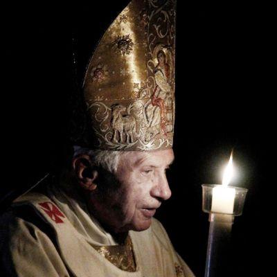 Paavi pitelee kynttilää pimeässä.