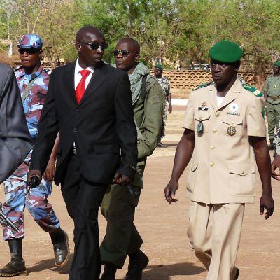 Barettipäinen kapteeni kävelee sotilaiden ja turvamiesten ympäröimänä.