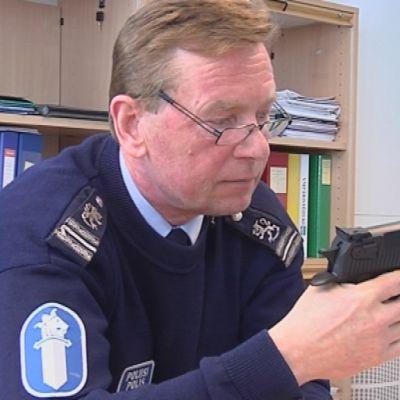 Komisario Arto Rajala esittelee aidon aseen näköistä kuula-asetta.