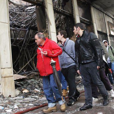 Miehet kulkevat tuhoutuneen rakennuksen editse.